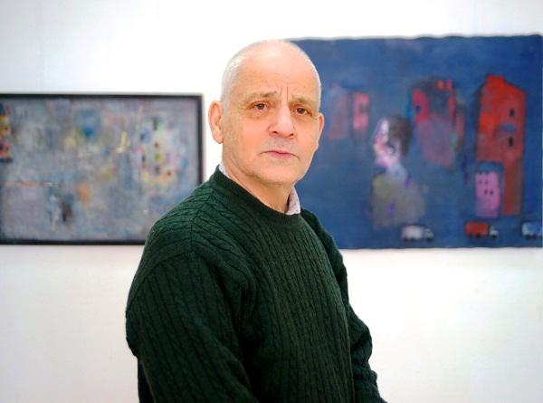 Художник  Лев Саксонов на фоне своих работ