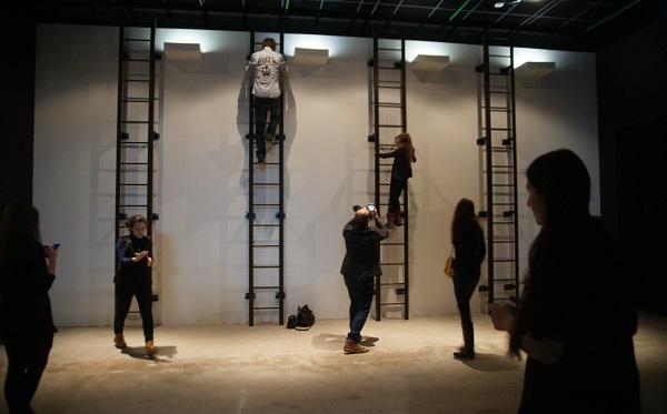 """МишМаш Инсталляция """"Земля-Небо"""" Выставка  """"Наверху"""" Музей Москвы 4  пожарные лестницы привинчены к стене с равными промежутками. На уровне верха лестниц, на стене, укреплены одинаковые белые параллелепипеды, из которых исходит белый свет.  Если смотреть снизу - видна холодная, минималистская, модернистская инсталляция:"""