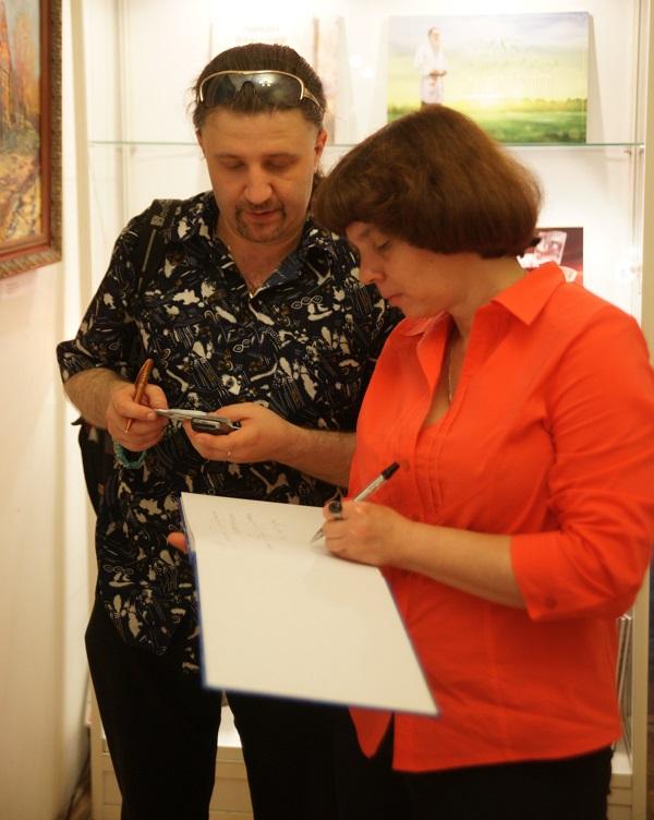 Маргарита Сюрина подписывает свой альбом гостю вернисажа