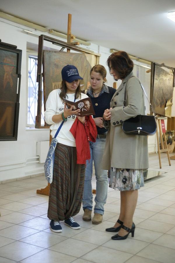 Гости вернисажа  рассматривают каталог выставки  Евгения Амаспюра