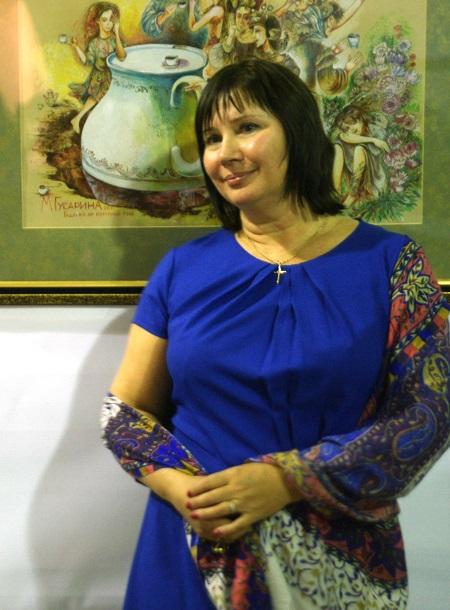 Художник Майя Гусарина на фоне своей работы в Творческой Мастерской Рябичевых