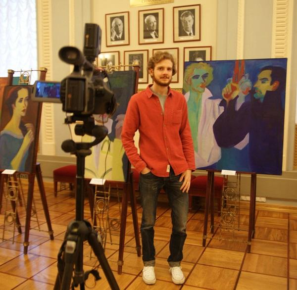 Актер Василий Симонов на фоне своего портрета, где он изображен в роли Ленского  художником Ильей Комовым