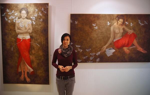 Художник  Минако Ота у своих картин в галерее Art-Constantis