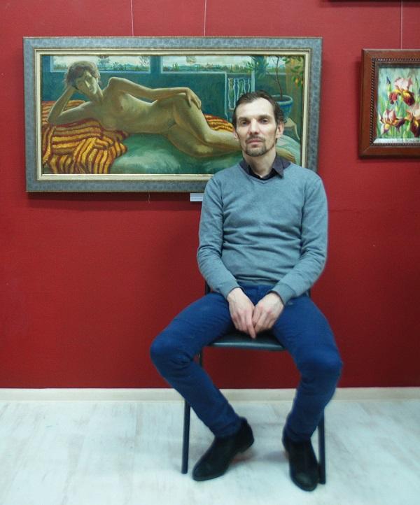 """Куратор выставки  """"Женщины и цветы. Весна"""" Алексей Гиляров на фоне своей работы"""