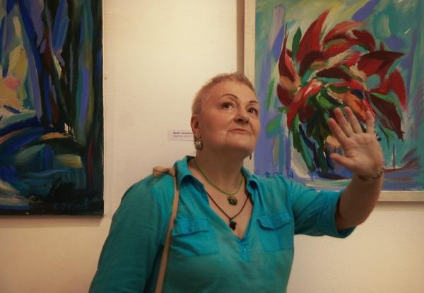 Художник Маргарита Юркова на фоне работ Евгения Окиншевича  на выставке в Российской Академии художеств 19 июля 2016 года