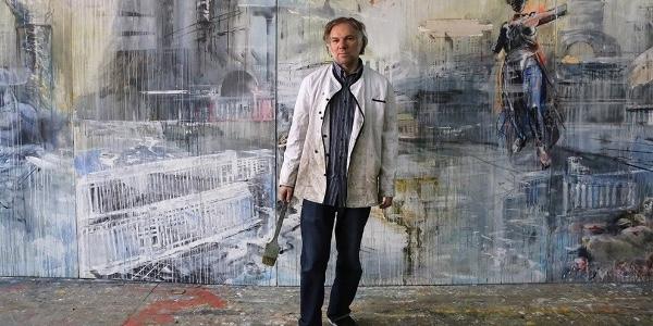 Художник  Валерий Кошляков на фоне своей работы