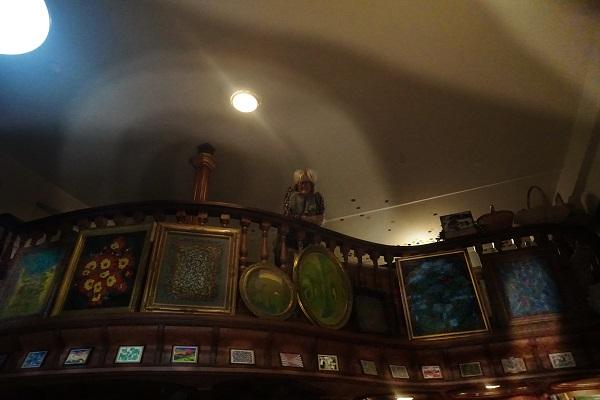 Жаклин Диана Мосс на фоне волшебного сияния мастерской, где картины, творческая обстановка  и освещение создают необычную атмосферу