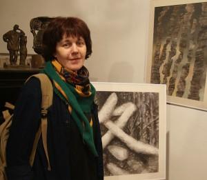 Художник  Мария Орлова  на фоне своих работ