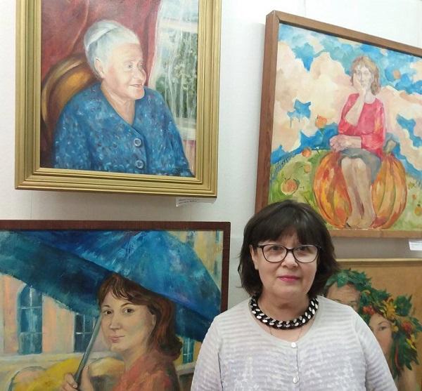 """Лидия Тихонравова на фоне своей работы (слева верхняя) в ЦДХ Выставка """"Портрет. Абстракция"""", 2017 год"""