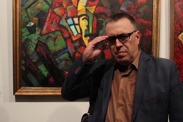 Художник  Ансар Галин  на фоне своей картины