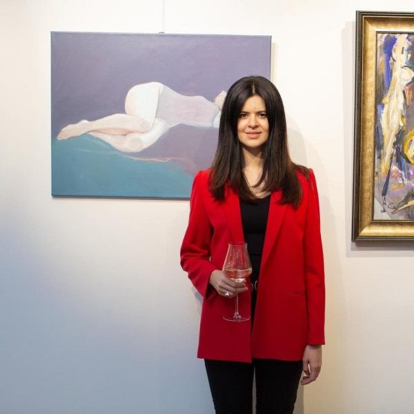 Автор выставки София Акимова на фоне своих работ