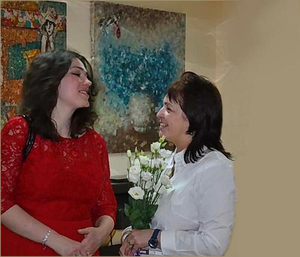 Мария Туманова, художник, поэт, организатор выставки с гостьей вернисажа на фоне картин  Воввы Морозова