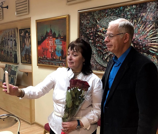 Мария Туманова с гостем выставки на фоне картин  Воввы Морозова